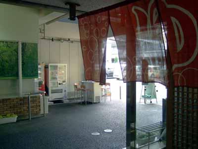 京都伏見力の湯の出入口に置かれる緑の募金型自動販売機
